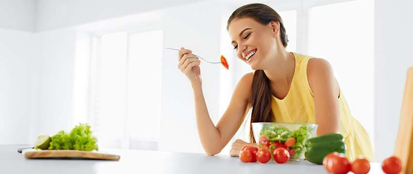 smiling woman with fruits and vegetables in the kitchen