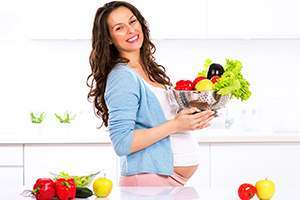smiling pregnant woman holding fruits and vegetables in colander
