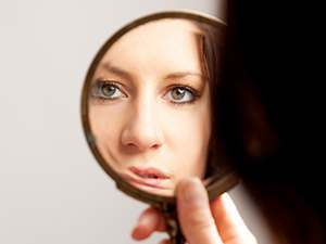 photo of a woman looking her self at the mirror