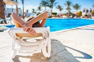 woman sun bathing beside the swimming pool