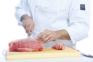 chef sliced raw meat using knife and chopping board