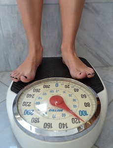 Woman Stepping on Weighing Scale