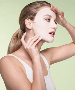 Woman Applying Sheet Mask on Face